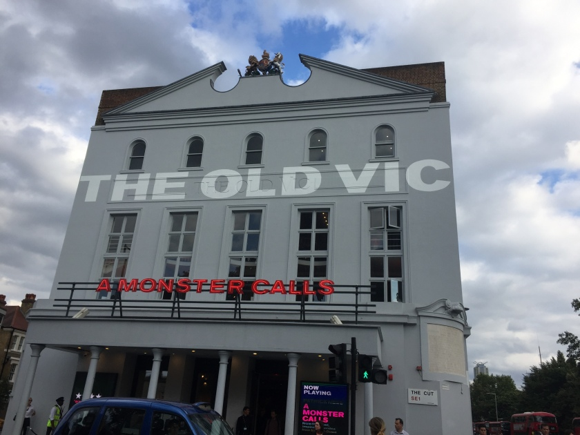 The outside of the Old Vic theatre building, with the words The Old Vic in big white letters across the wall between the rows of windows. Above the theatre entrance are red letters that say A Monster Calls.