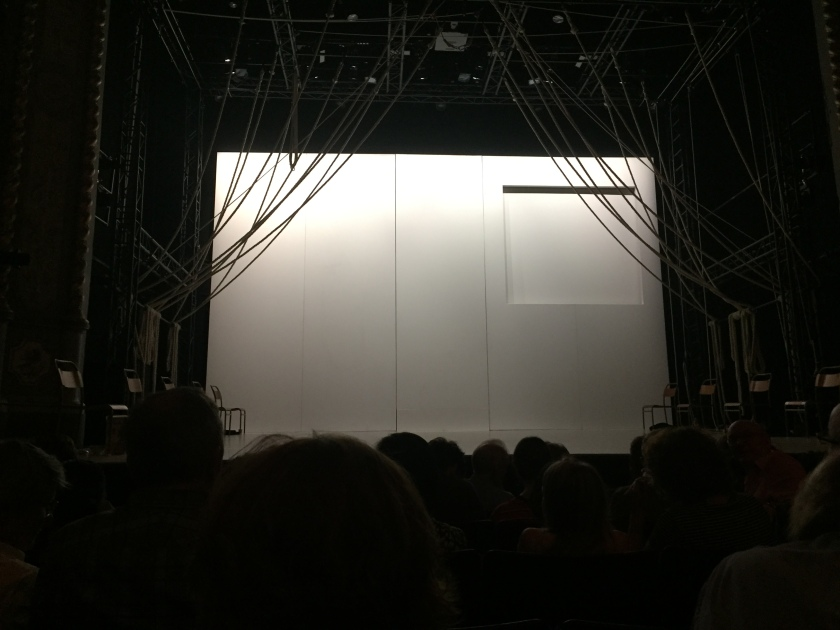 The empty stage for A Monster Calls. The floor and back wall of the stage are white, and at the top right of the back wall is a large square panel inset from the rest of the wall. Lengths of rope extend down from the ceiling and curve across to each side of the stage where they're held in place.
