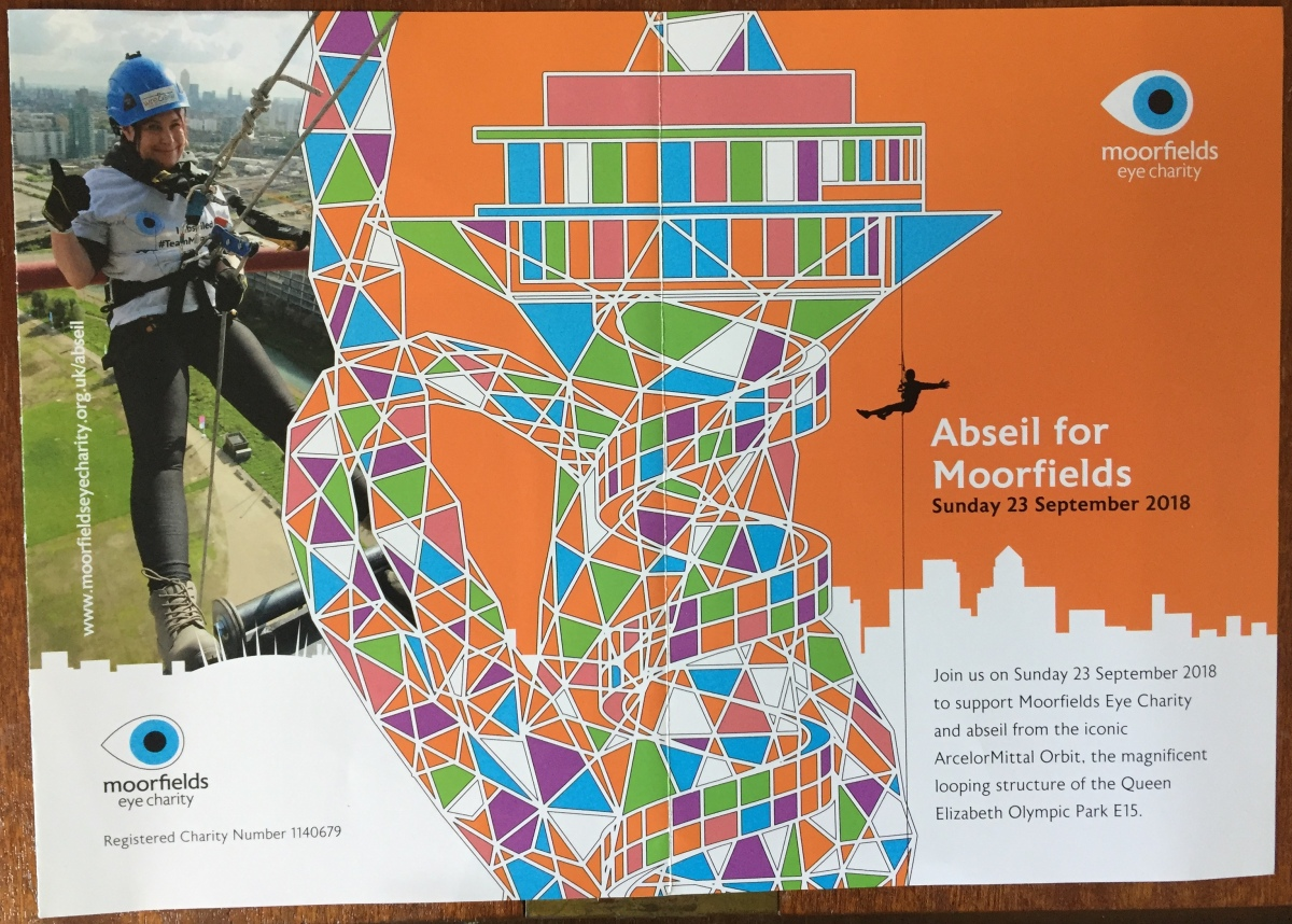 Leaflet called Abseil For Moorfields. Central image shows a multi-coloured illustration of the Orbit Tower, a tall structure with lots of curves and a helter skelter slide running down the outside. To its left is a photo of a lady waving as she prepares to do her abseil. To the right is text inviting people to join in the abseil on Sunday 23rd September 2018.