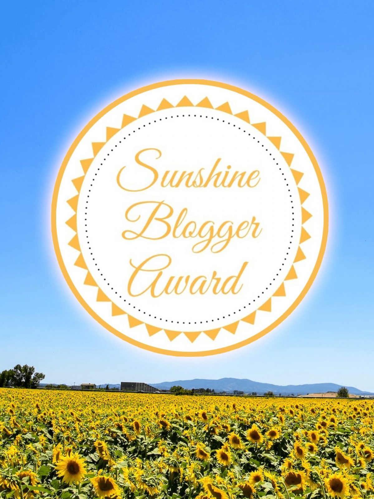 Above a field of yellow flowers, against a clear blue sky, is a large white circle, with a yellow border made up of little triangles like the pointed border of the sun. In the centre of the white circle is large yellow text, in a curly script font, that says Sunshine Blogger Award.