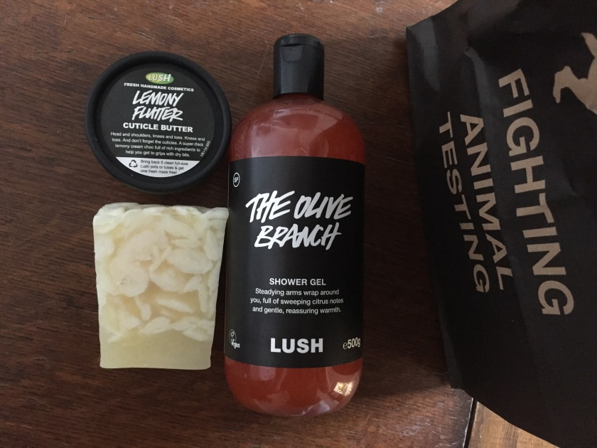Lush Purchases - a big bottle of The Olive Branch shower gel, the contents of which is red in colour, a bar of the creamy yellow coloured Bohoemian Soap, and a small round pot of Lemony Flutter Cuticle Butter. The items are sat next to a bag that has Fighting Animal Testing on it in capital letters.