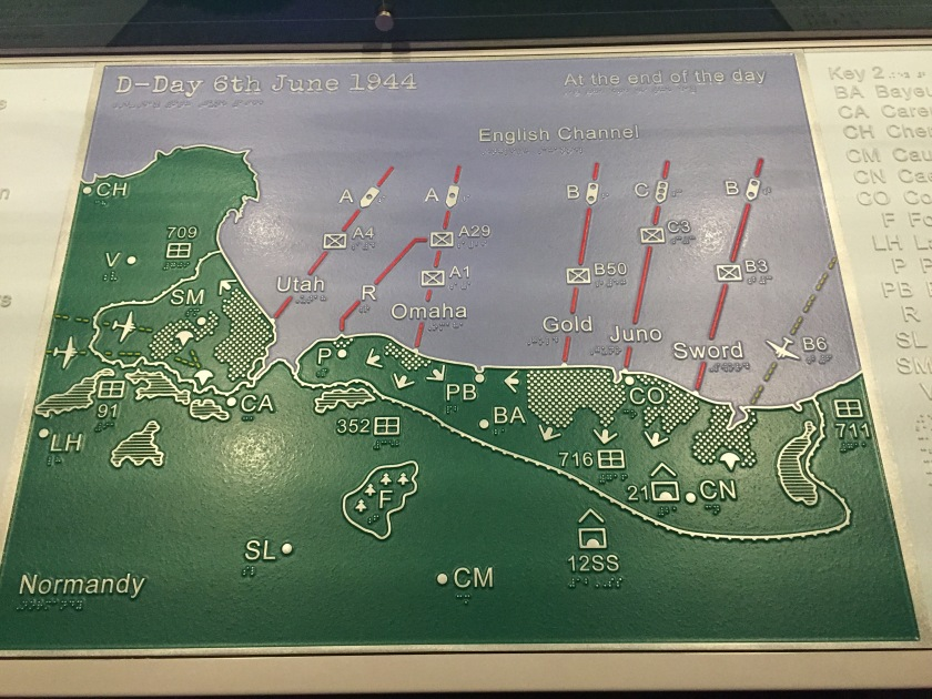 A map of Normandy on D-Day, entitled At The End Of The Day. The land is coloured green with white edging and the sea is in blue. The map is covered in lines and arrows showing the movements of ships in the English channel and personnel on the land. The names of the 5 beaches are also shown in white - Utah, Omaha, Gold, Juno and Sword.