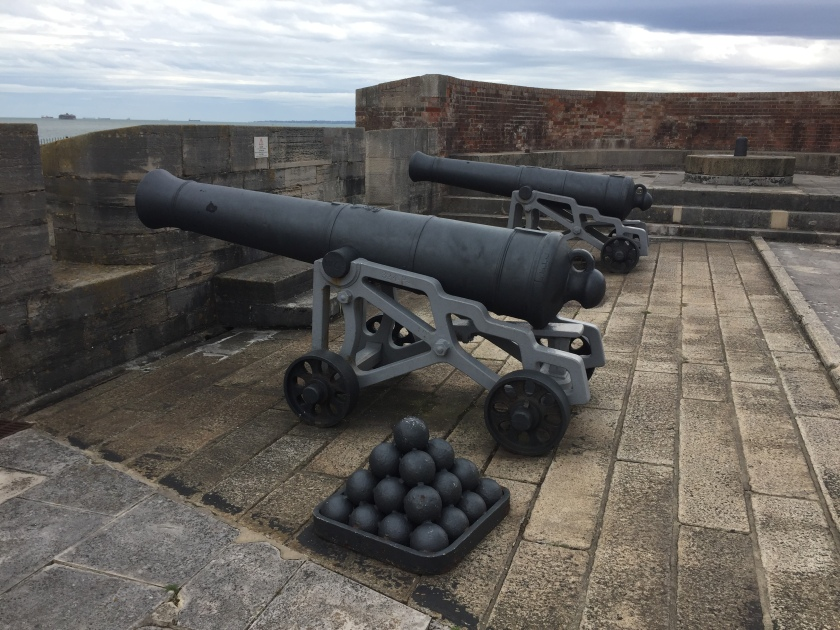 2 large cannons and a pyramid stack of cannonballs on top of Southsea Castle.