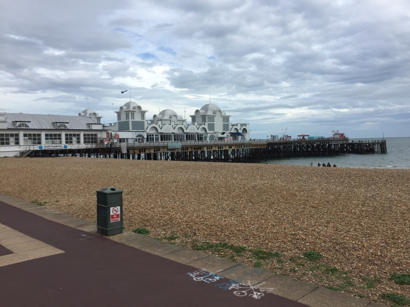 South Parade Pier, a long pier stretching out to sea. The white building on top, stretching from the shore to the centre of the pier, has a few arches on the side as part of its design.