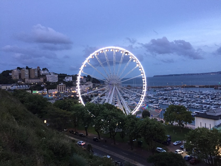 View towards Torquay from the top of the cliffs in the early evening light. A massive white ferris wheel, on which people can ride to enjoy the views, dominates the centre of the image. Behind this is the harbour area to the right with rows of boats, and the town to the left. Below the wheel, the main road is visible, with trees lining the pavement in front of the wheel.