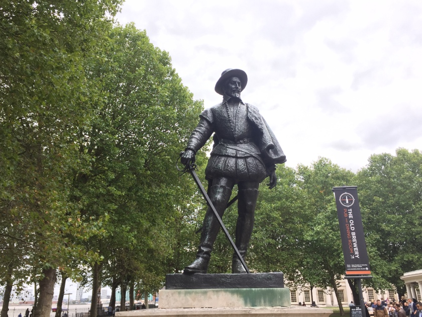 Statue of Sir Walter Raleigh, a bearded gentleman wearing a hat and a jacket that puffs out slightly around the waist, while holding a cane in his right hand that reaches down to his left food.