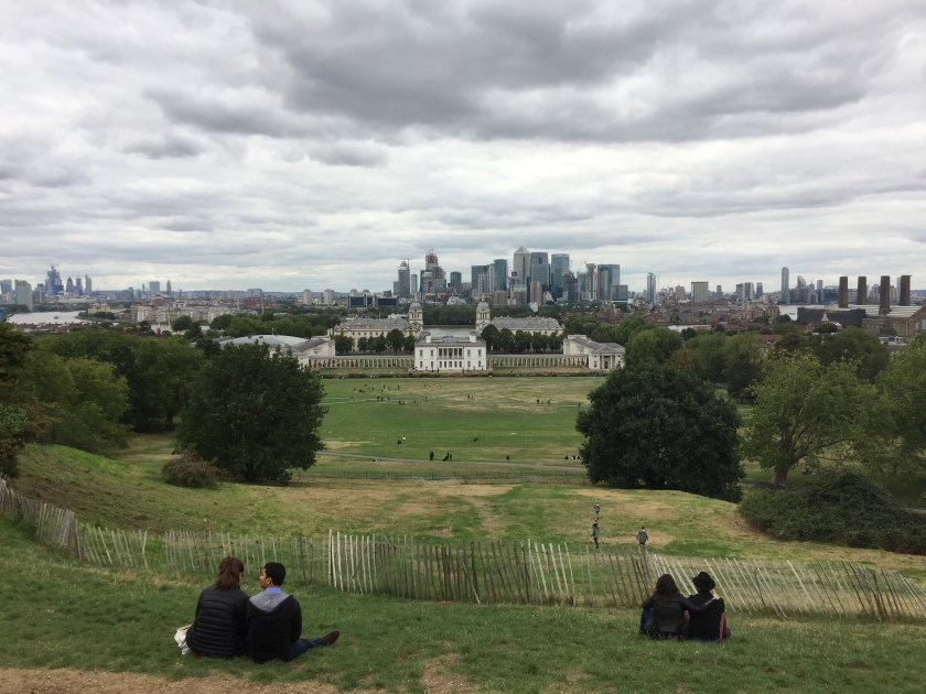 View of the London skyline from the top of a large grassy hill in Greenwich Park.