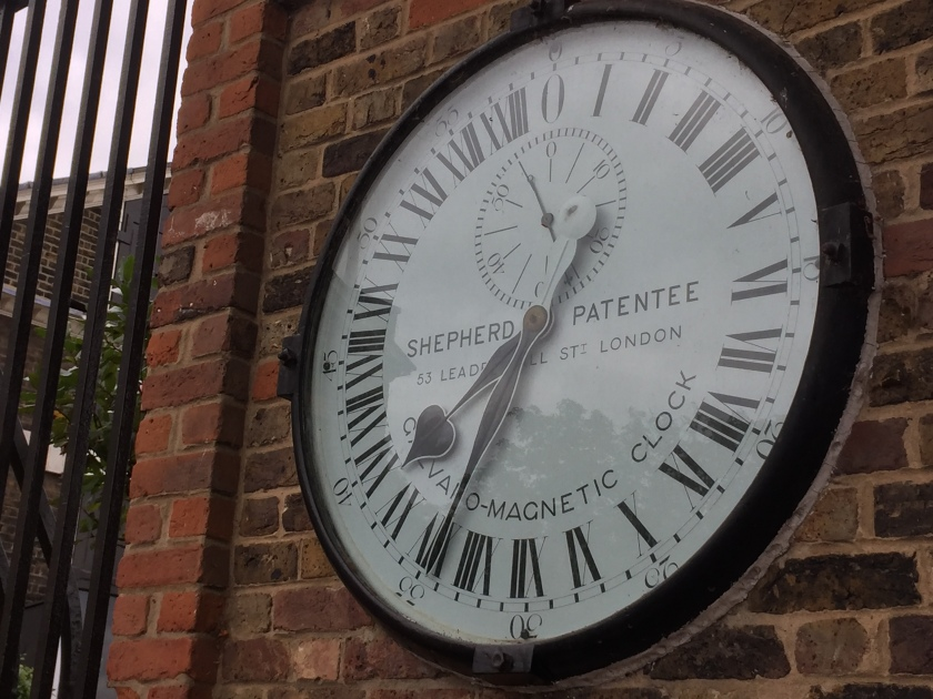 The Shepherd's Gate Clock - a large white clock face with black hands, and black Roman numerals around the edge that go up to 24 hours instead of 12.