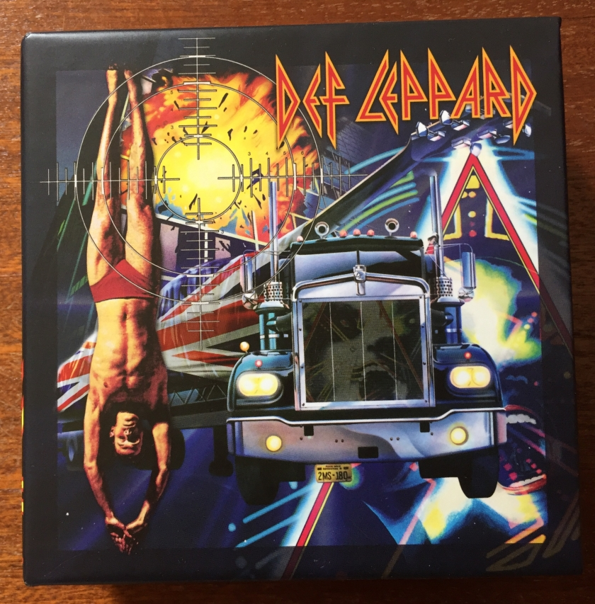 Cover for the Def Leppard CD Collection Volume 1 boxset. The cover mixes imagery from the album covers in the set, including a speeding truck, a man diving, an explosion, and the triangular logo from Hysteria.