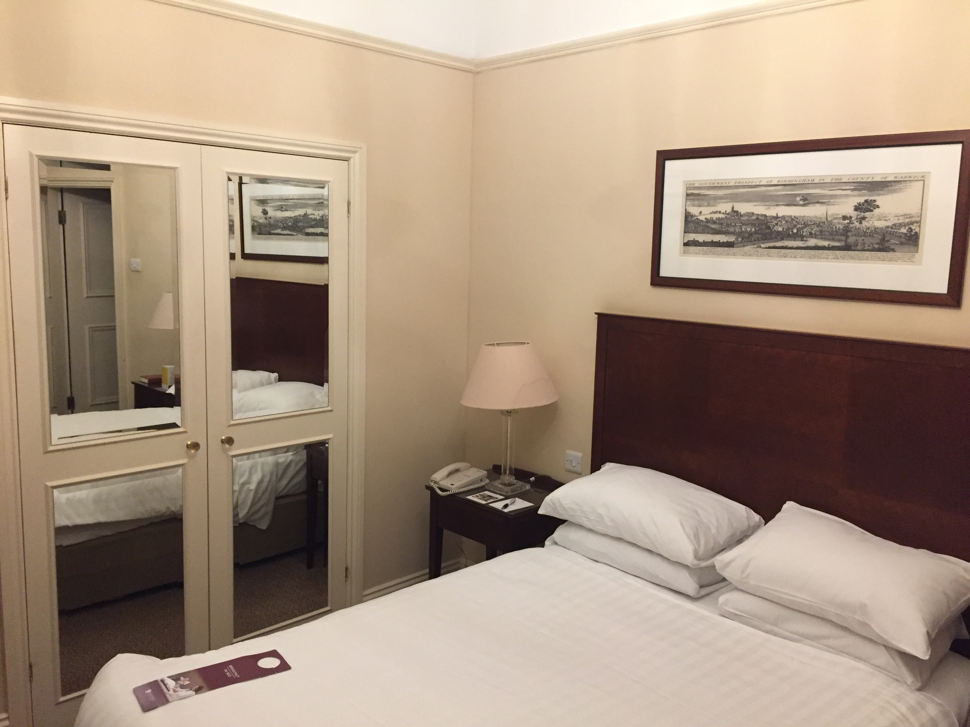 Hotel room with a double-bed next to a wardrobe with mirrored doors. In the reflection on the doors you can see the entrance to the en-suite bathroom on the other side of the room.