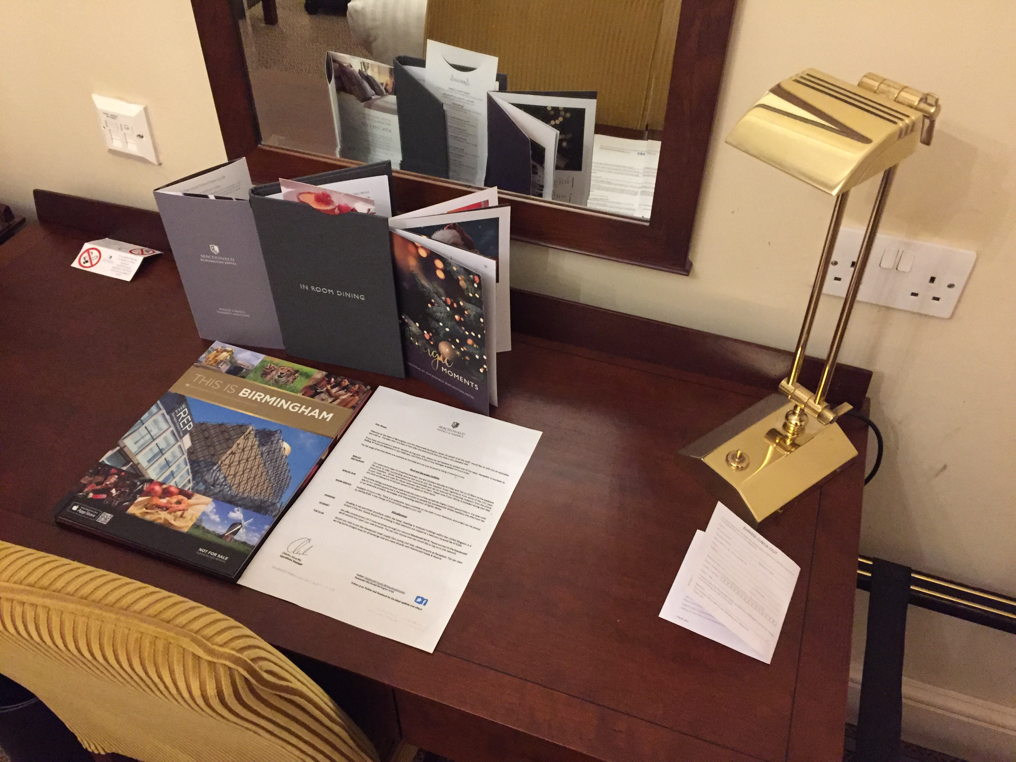 Desk in my hotel rom, with a gold coloured reading lamp, a welcome letter, a hardback book called This Is Birmingham, a leaflet about the hotel, a room service dining menu, and a booklet about their Christmas events. A large mirror is on the wall above the desk.