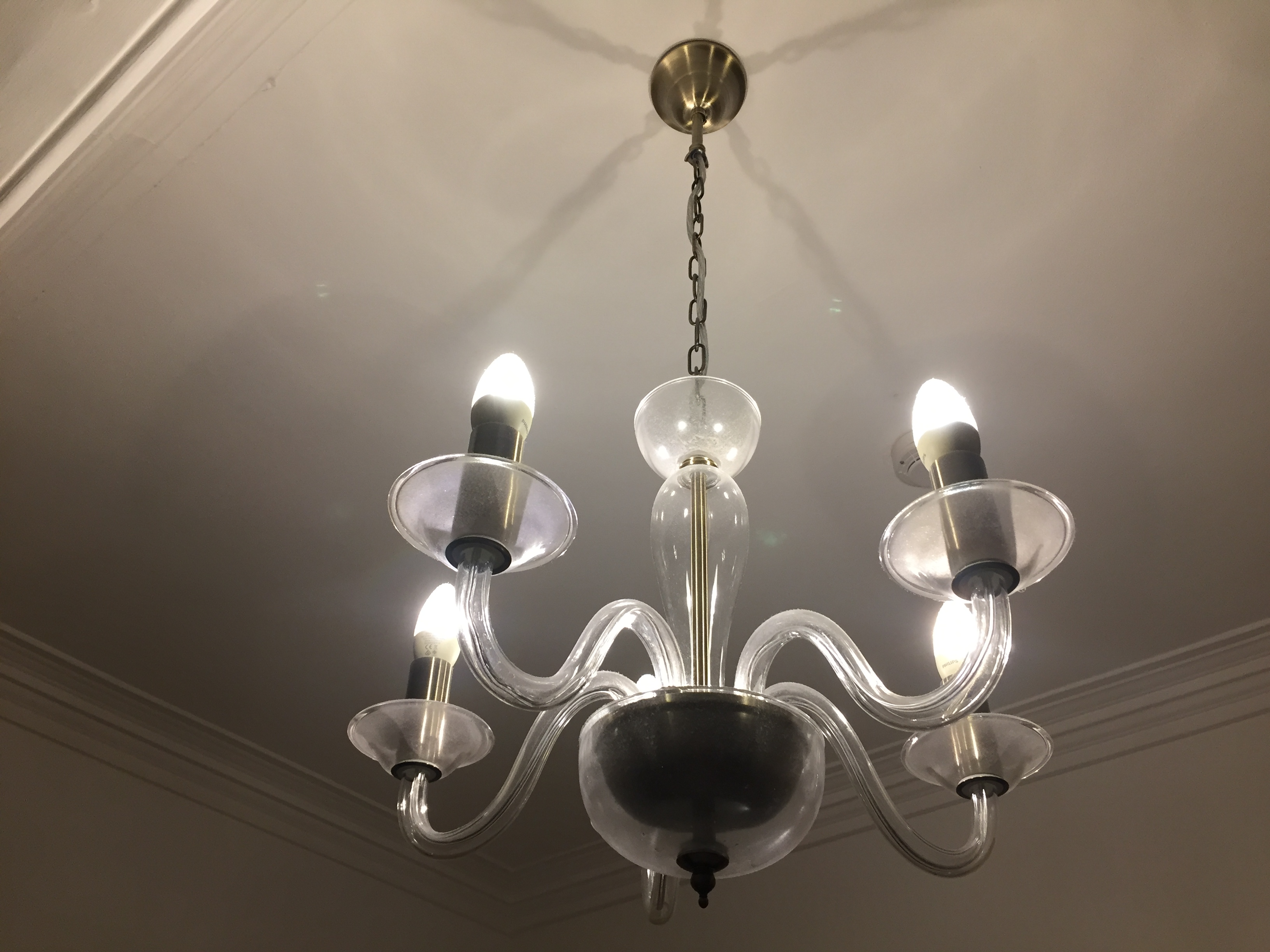 Small chandelier on the hotel room ceiling, with 4 lights held up on snaking glass poles coming out from the centre.