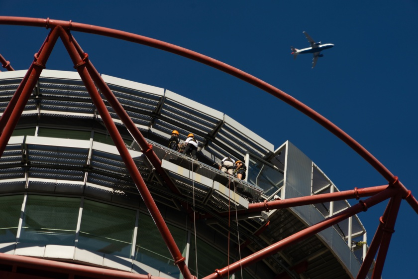 Photo taken by a spectator on the ground, zoomed in on Glen and Claire standing on the abseil platform at the top of the tower as a large plane flies overhead.