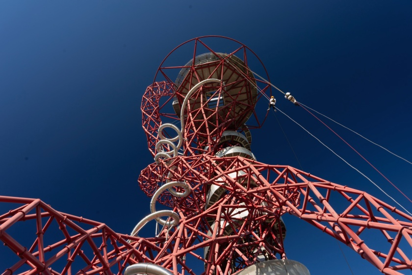 Photo by a spectator on the ground almost directly below the tower, looking up towards the underside of the circular platform at the top. The photo is zoomed out so that most of the tower is visible. Claire and Glen can be seen abseiling on the right side of the tower.