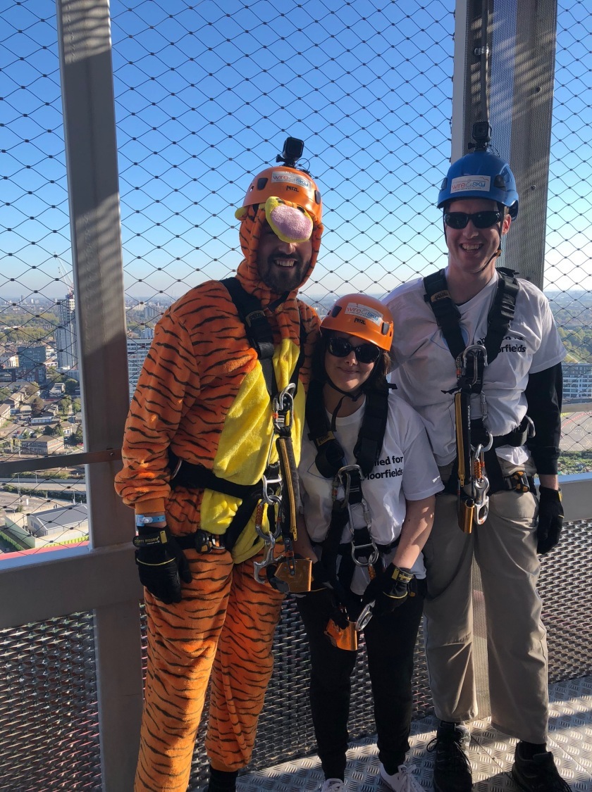 Matt, Claire and Glen ready to abseil in their harnesses and helmets. Matt and Glen also have GoPro cameras attached to their helmets. Glen and Claire are wearing their Moorfields Eye Charity t-shirts and normal trousers, but Matt is wearing an orange furry Tigger bodysuit, to look like the character from the Winnie The Pooh stories, with black tiger stripes, a yellow chest, and a big round grey nose poking out from under his helmet.
