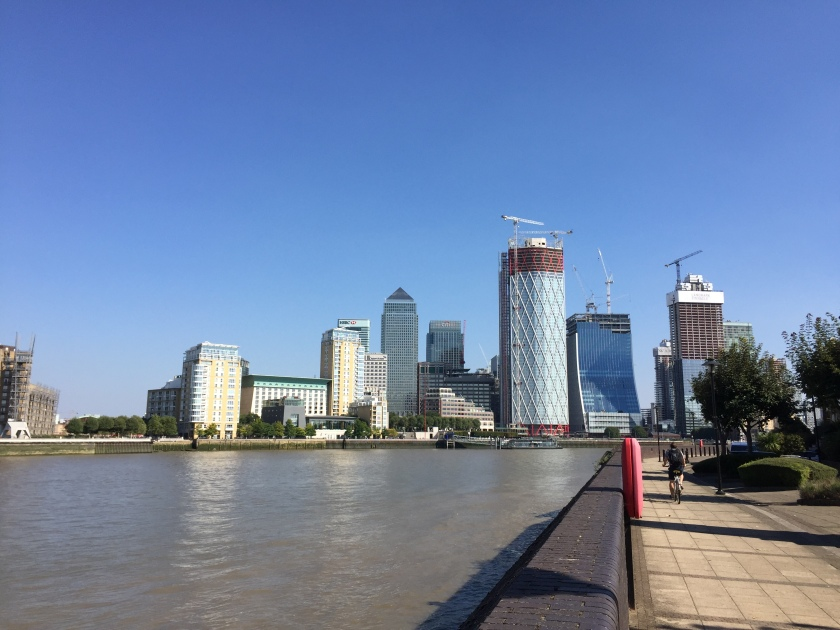 View along the River Thames from the Thames Path. Canary Wharf and other skyscrapers are on the bending curve of the river ahead, under a clear blue sky.