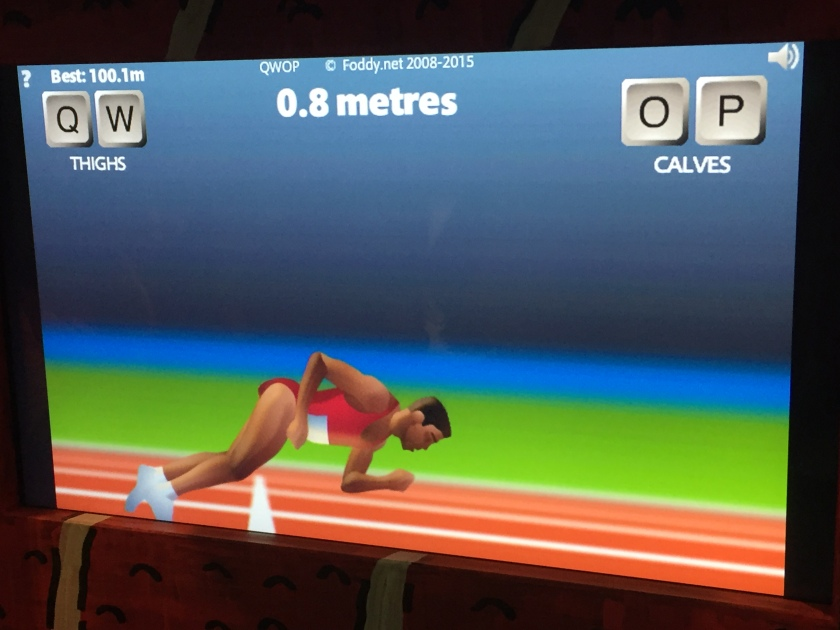 The computer game QWOP. The athlete on the screen, wearing a red top and shorts, is falling face first on to the running track, just over the start line. Text at the top says the distance covered is just 0.8 metres.