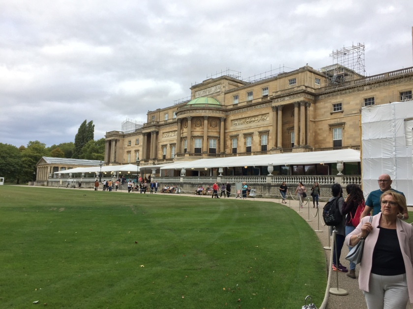 Rear view of Buckingham Palace, which overlooks a large lawn.