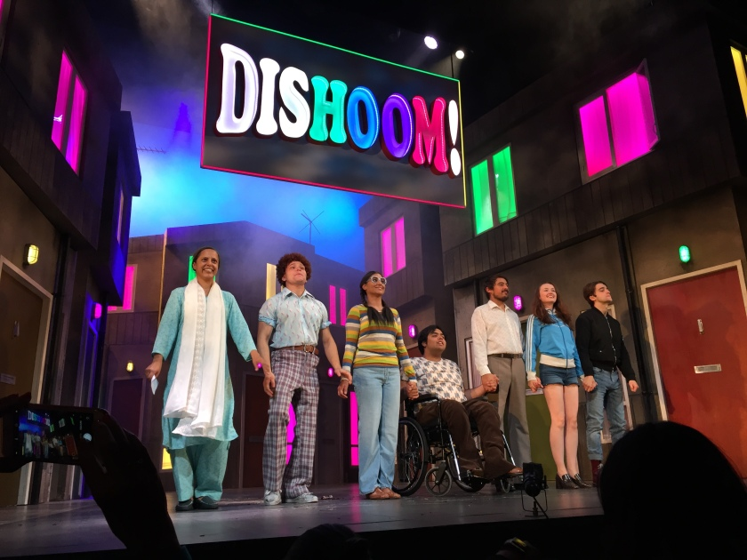 The cast of Dishoom standing in a line on stage holding hands. The central character in the line of 7 people is a man in a wheelchair. Behind them is a street with large houses on either side, the windows lit up in green and pink colours. Above them is a large sign saying Dishoom! in multi-coloured lettering.