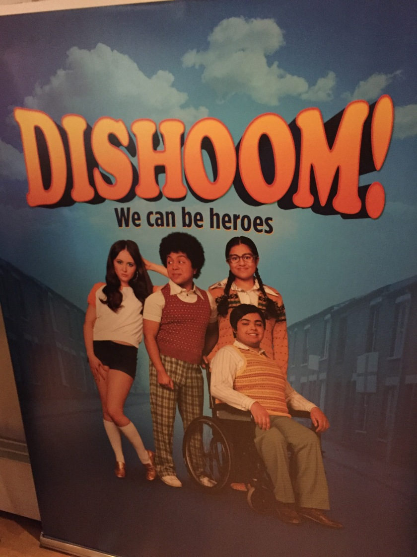 Poster for Dishoom!, with the strapline We Can Be Heroes. Below the text is a picture showing the main character, a young man in a wheelchair, with 3 of his friends behind him (1 male and 2 female).