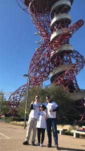 Glen, Claire and James smiling and giving a thumbs up, posing in their Moorfields Eye Charity abseil t-shirts, as the Orbit Tower stands high over them in the background.