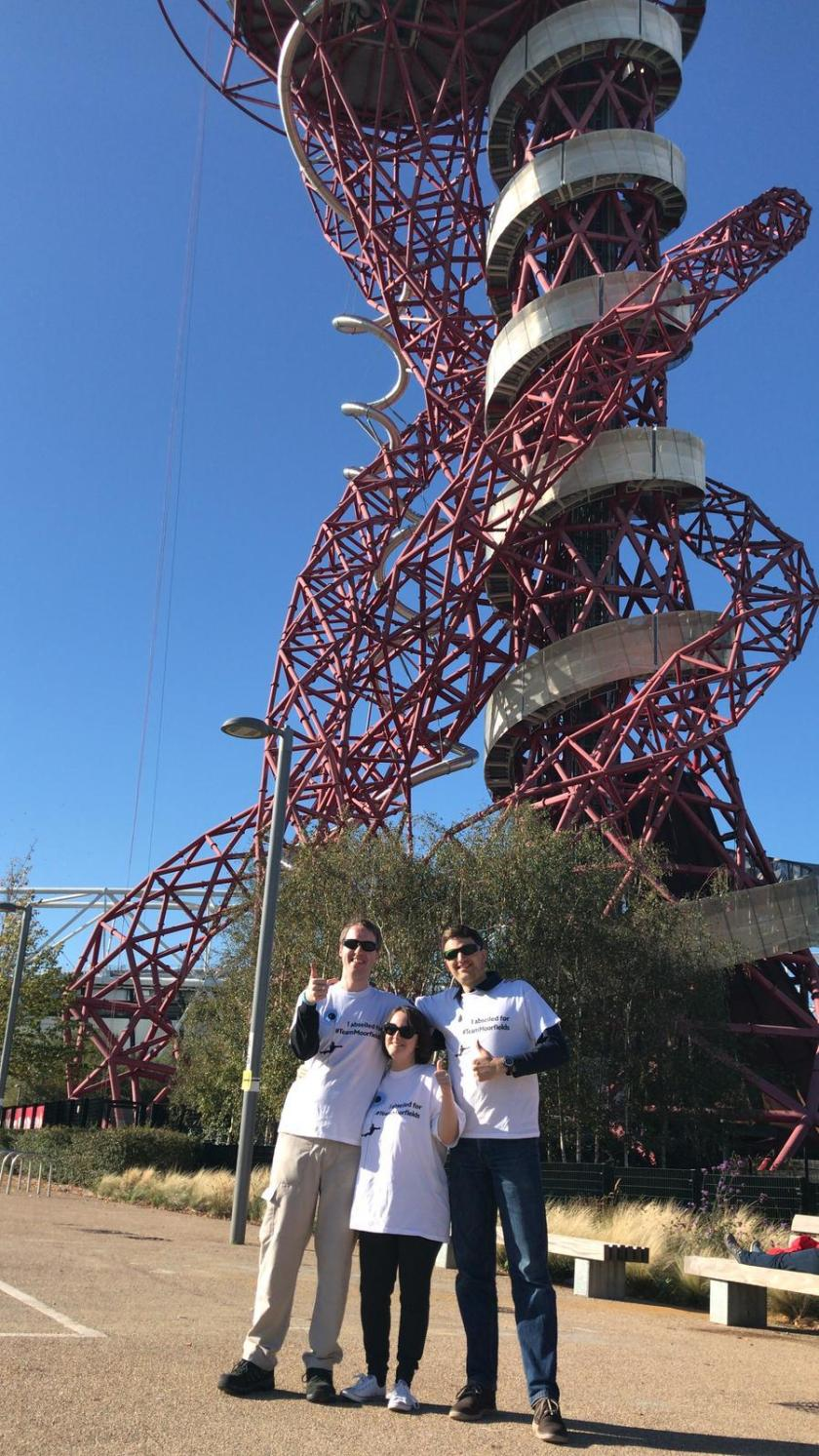 Glen, Claire and Vicky smiling and giving a thumbs up, as the Orbit Tower stands high over them in the background.
