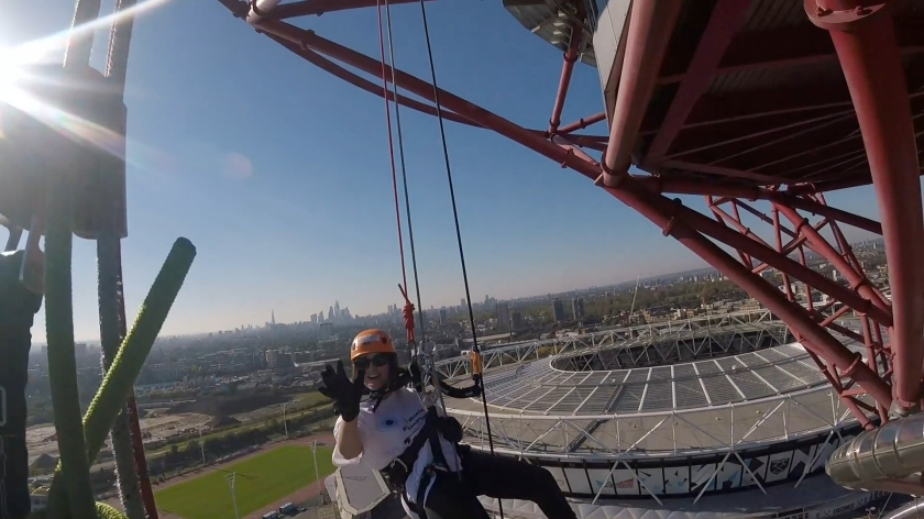 Headcam view to the right of the tower, showing fellow abseiler Claire smiling and waving, with the large round Olympic Stadium behind her, and the London skyline stretching into the distance.