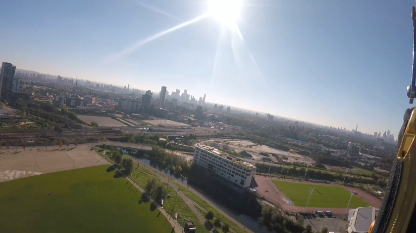 Another headcam view of the Olympic Park and London skyline, taken slightly further right of the previous one. This angle reveals some of the large grassy area directly below, where people were cheering on the abseilers, plus a large rectangular patch of grass slightly further away on the right, possibly a football training pitch.