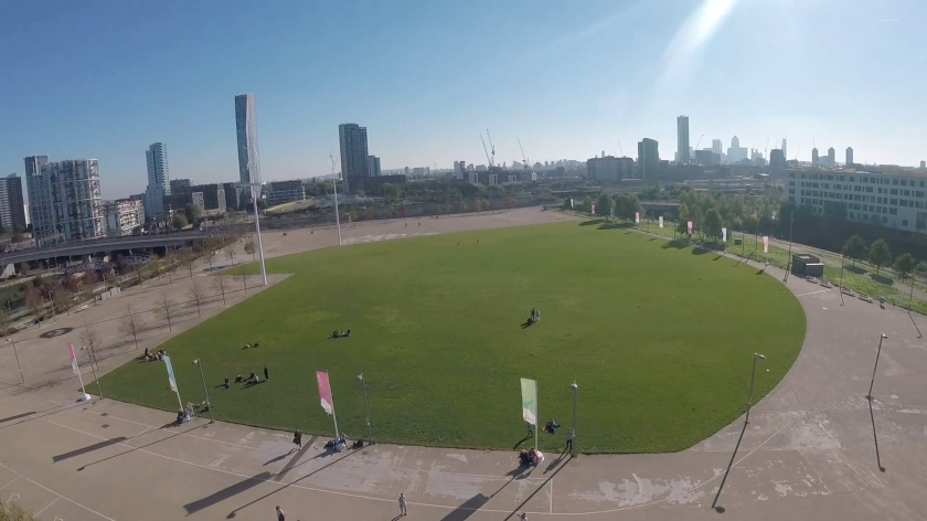 Headcam view of the large round grassy area where spectators can watch the abseil, with a few small trees along the left and right sides, and buildings of various heights across the background in the distance.