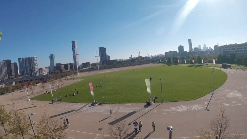Headcam view of the large round grassy spectator area from a slightly lower angle. This time, on the large concrete area surrounding the grass, a few friends can be seen waving at the bottom of the photo.