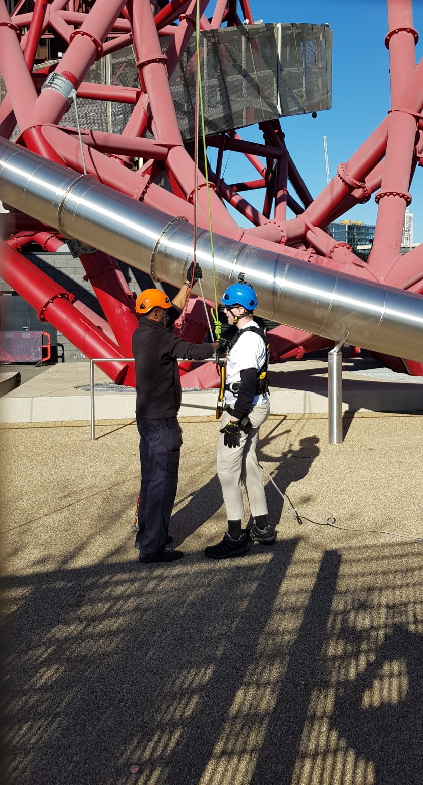 Now standing back on the ground, Glen waits as the male instructor disconnects the ropes from his harness. Part of the large metal slide around the tower can be seen curving towards the ground behind them, the end being somewhere to their right.