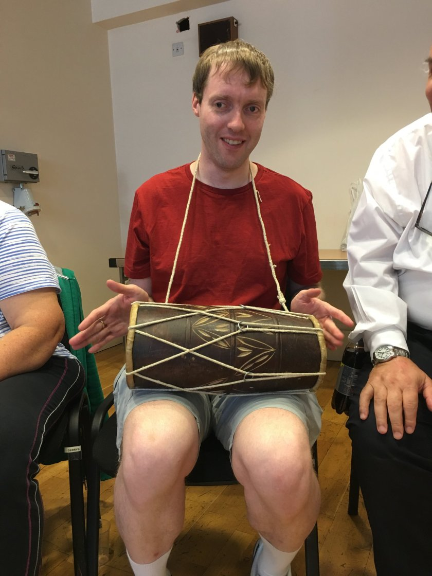 Glen sitting and smiling with a long wooden drum across his lap. It has lengths of string that cross over as they stretch from one end of the drum to the other in diagonal lines. A further length of string goes around Glen's neck, with each end attached to the side of the drum. Glen's hands are positioned on each side of the drum, ready to tap out a beat using both ends of it.