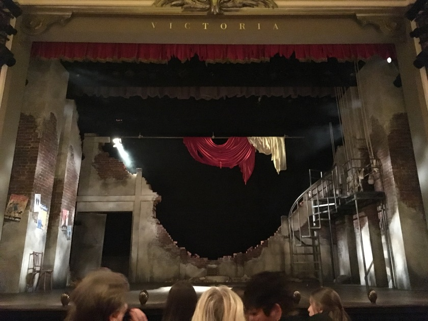 The stage for Much Ado About Nothing, designed to look like a bombed out theatre from the 1940s, with a huge hole in the back wall left behind by a bomb. Torn remnants of green and red fabric hang in the air above it. 2 rectangular pillars on the left of the stage have a few war posters on them, while on the right a spiralling staircase leads up to a balcony.
