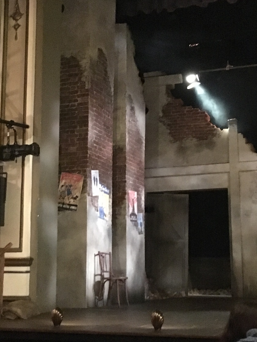 View of the left side of the stage for Much Ado About nothing, showing the 2 tall square pillars. As the set resembles a bombed out theatre from World War 2, the pillars are damaged, with a lot of the white paintwork stripped away revealing the bricks underneath. On the bottom third of the pillar, where most of the white paint remains, various posters from the war are attached.