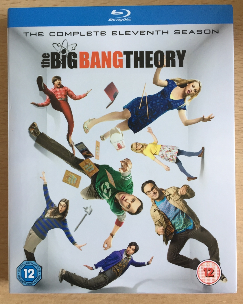 Front cover of the Blu-ray for The Big Bang Theory Season 11, showing all the main characters striking different poses as their individual photos are positioned in various angles and directions.
