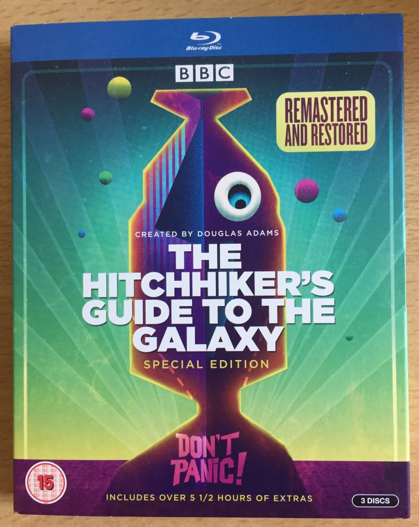 Front cover of The Hitchhiker's Guide To The Galaxy Special Edition Blu-ray, with a rocket in the shape of a fish front of a green and blue sky that has planets of various colours.