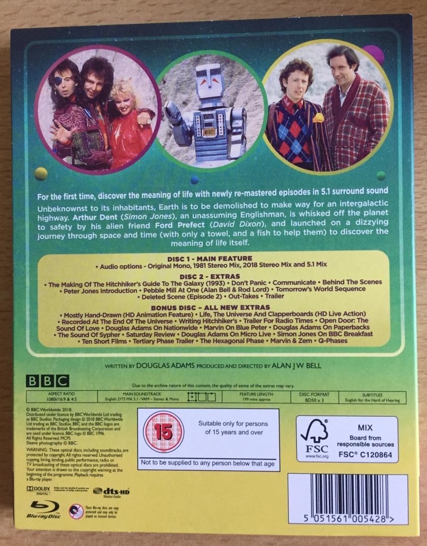 Back cover of The Hitchhiker's Guide To The Galaxy Special Edition Blu-ray, with a synopsis of the story and photos of the main characters. Audio options include the original mono mix, stereo mixes and a surround sound mix. Special features include many behind the scenes details about the series and interviews with Douglas Adams, plus a deleted scene, outtakes and a trailer.