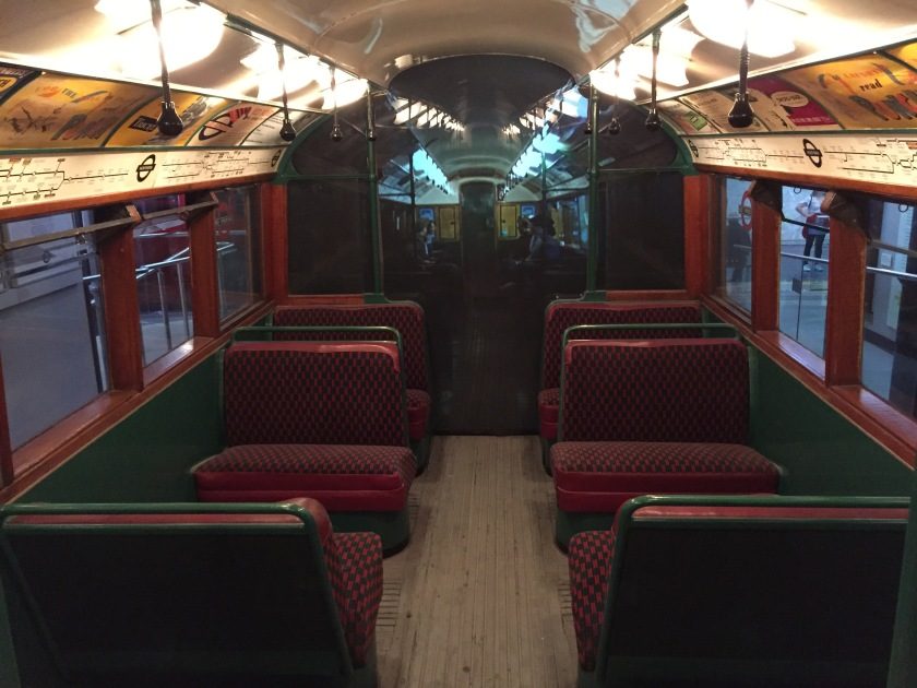 The interior of a 1938 stock tube carriage. The red seats are aligned across the carriage with a small aisle between them, unlike modern Tube trains where seats are aligned along the sides of the carriage. Above the windows on each side of the carriage is a map of the Tube line and various advertising posters.