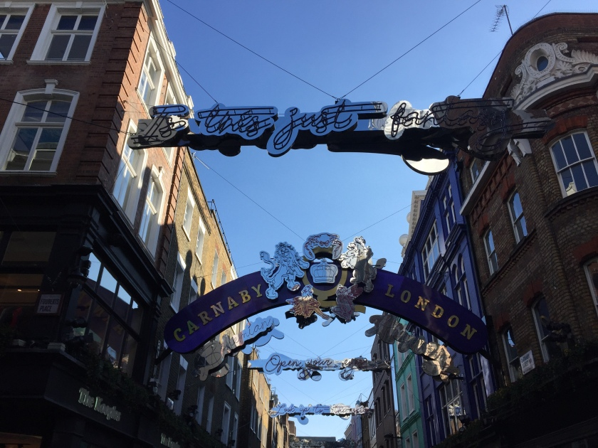 In the daylight, decorations promoting Queen in the air across Carnaby Street. A silver version of the band's crest, with a lion on each side of the central crown, sits in the centre of a curving blue archway that says Carnaby on the left and London on the right in gold letters. Other decorations stretched across the street quote lyrics from Bohemian Rhapsody in curly script lettering, e.g. Is This Just Fantasy, Open Your Eyes, and Look Up To The Skies.