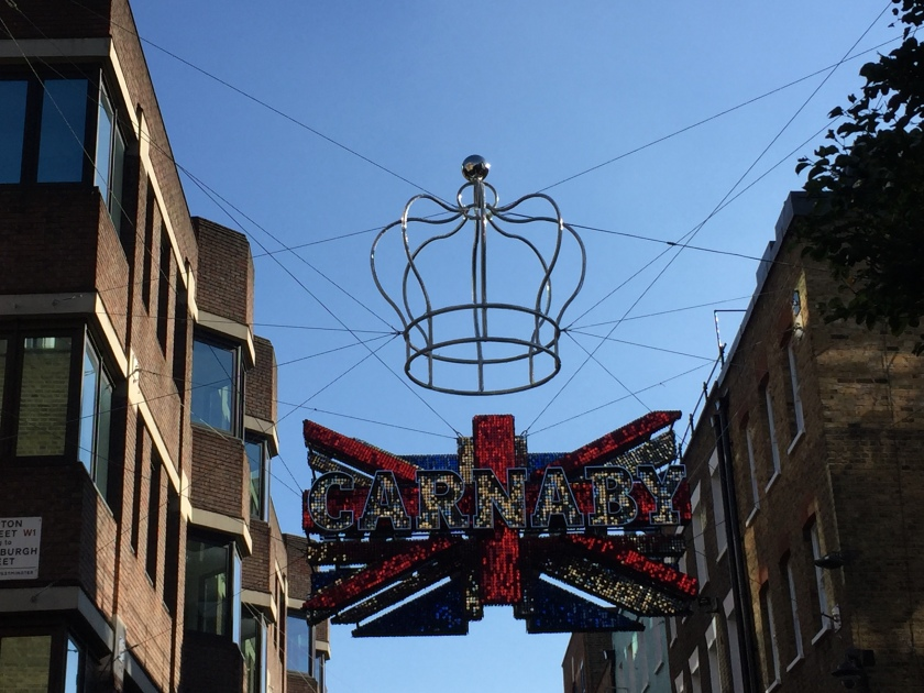 In daylight, a hollow outline of a crown with curving sides instead of spikes hangs over a Union Jack sign with the word Carnaby across it in big white letters.