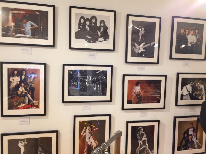 Photo gallery on the wall in the Queen shop, with pictures of Queen and Freddie Mercury in promotional shots, working in the studio and performing live on stage.