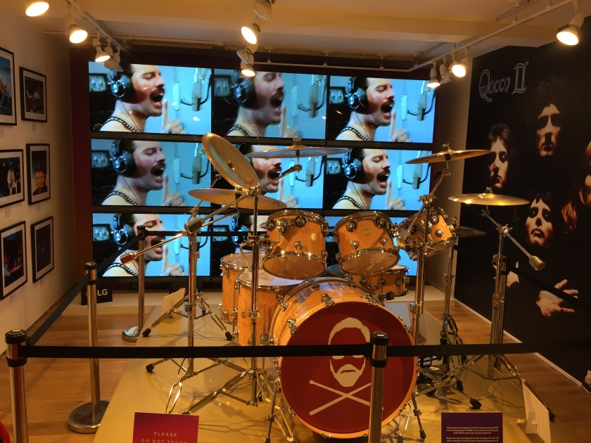 A drum kit used by Roger Taylor on display in the Queen pop-up shop. The front of the drum in the centre has a simple silhouette of Roger Taylor's head among 2 drumsticks laid in an X shape. Behind the drum kit, a grid of 9 screens are all showing the same video of Queen recording One Vision in the studio, with Freddie Mercury singing into the microphone. To the right of the kit and screens is a large poster of the Queen 2 album cover, showing all 4 members of the band.