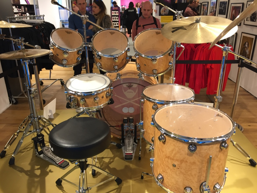 Rear view of Roger Taylor's drum kit in the Queen shop, showing the stool he would sit on and the view of the drums and cymbals that he would have had. There are 2 hi-hat cynbals on the left and 2 larger symbols on the right. Above the bass drum in the centre are 3 drums angled towards the drummer, , and another smaller drum at a flatter angle just in front of the stool. To the right are 2 more large drums below the big cymbals.