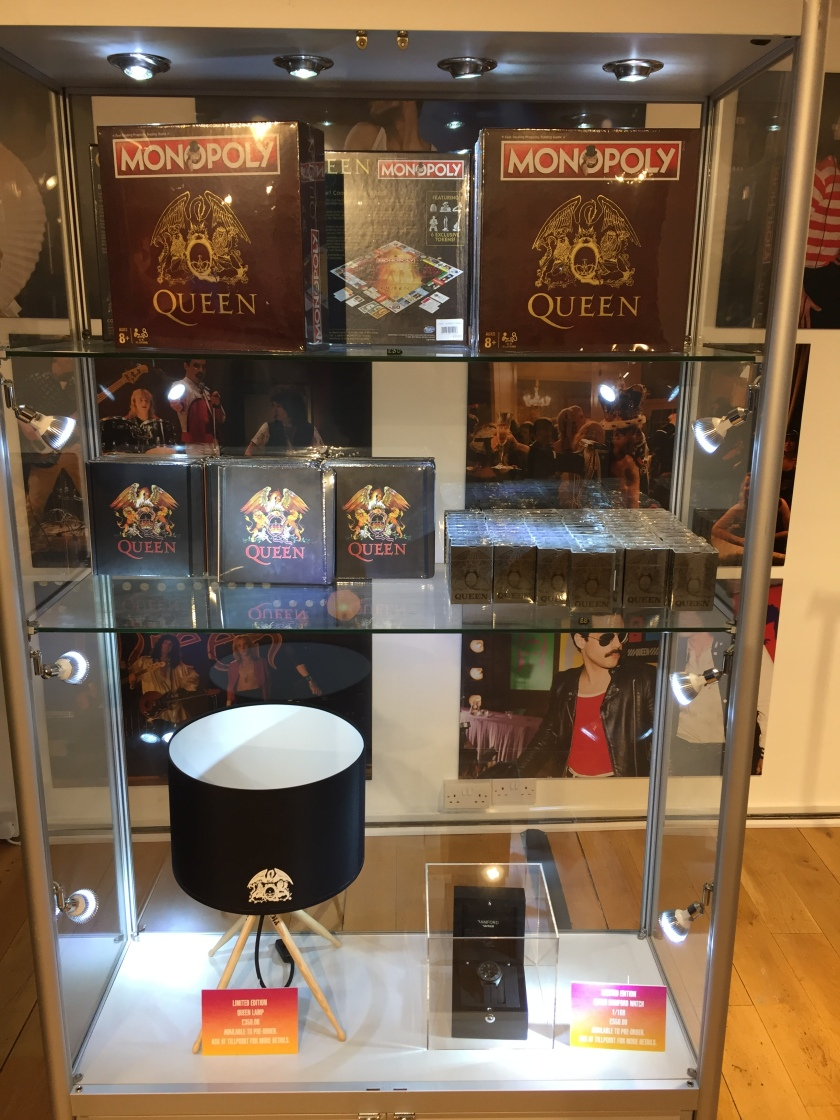 Glass shelving in the Queen shop featuring Queen Monopoly, playing cards, notebooks, a limited edition lamp and a limited edition watch.