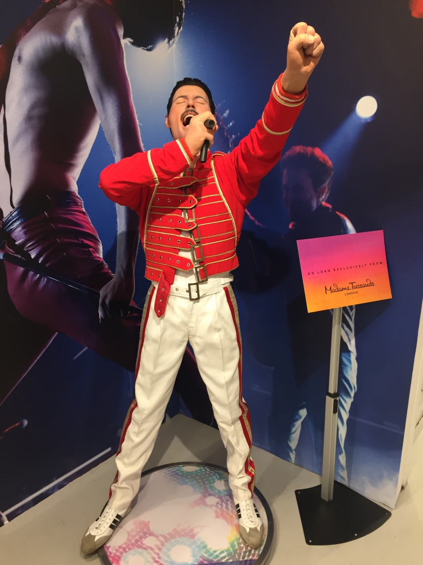 Statue of Freddie Mercury, wearing a red jacket with gold trim, and white trousers with red and gold stripes up the sides of each leg. Freddie's eyes are closed and his mouth is wide open, as he sings powerfully into the microphone held in his right hand, while his left arm is stretched high as he punches the air.