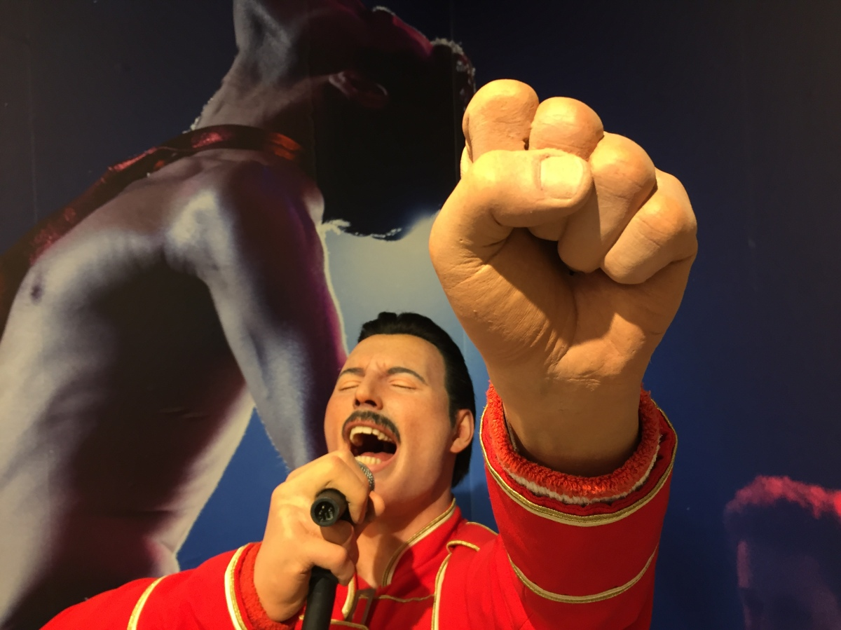 Close-up of the Freddie Mercury statue, with Freddie's fist punching the air close to the camera, as he sings powerfully in the background.
