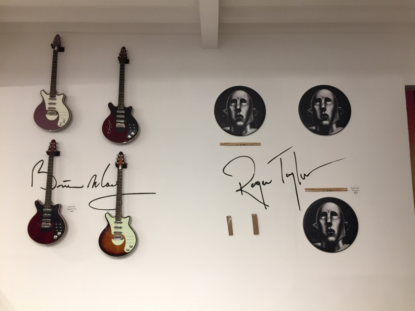 Wall display in the Queen shop with 4 electric guitars signed by Brian May, and drumsticks from roger Taylor.