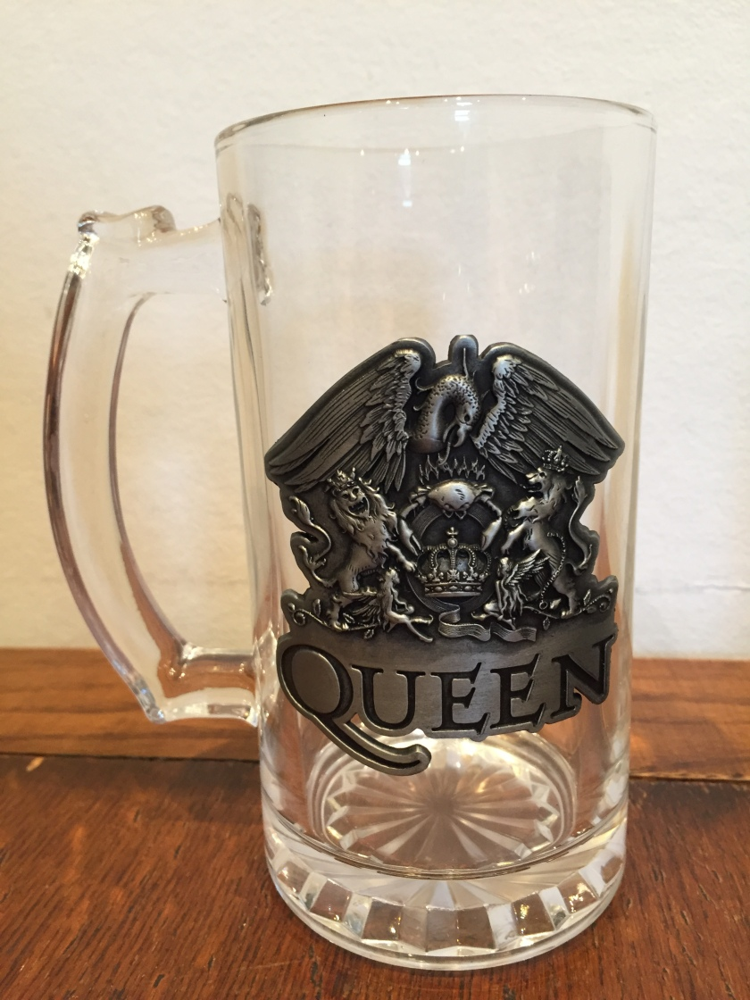 A large glass stein, basically a pint glass with a handle. On the side is a large metal version of the Queen crest. The crest has a large phoenix sitting on top of a large letter Q with a crown in the middle of it. 2 lions, one on each side, are holding up the letter Q with their front legs while standing on their back legs. The band's name is below the crest.