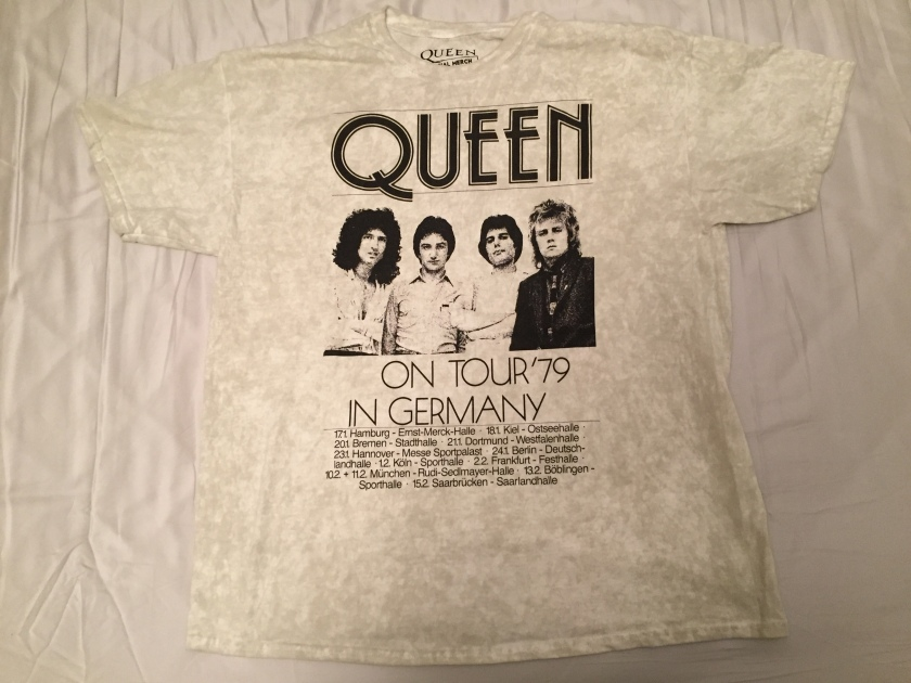 Short-sleeved t-shirt in a dirty white colour. From top to bottom, the black coloured design has the band name Queen in large letters, then a photo of Brian, John, Freddie and Roger, then large capital letters saying On Tour 79 In Germany, and finally 6 lines of much smaller text with the dates and venues from the tour.