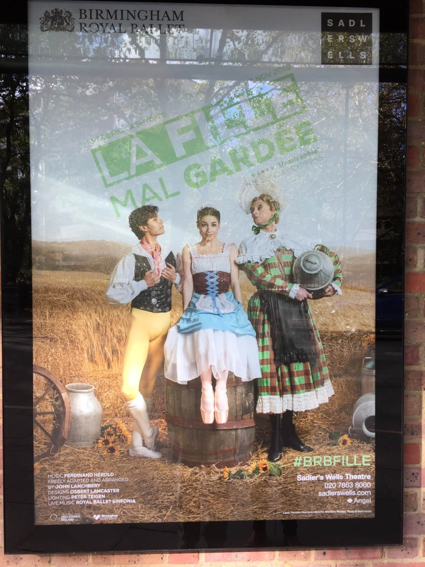 Poster for La Fille Mal Gardée, showing the 3 central characters in a corn field. The handsome man on the left has tight yellow trousers, a black jacket over a shirt with white sleeves, and a pink ribbon tied around his neck. He is looking lovingly at the young lady sitting on a barrel in the centre, whose dress has a flowing white skirt with a blue layer of fabric on top and a black chest section with criss-crossing blue fabric up the centre. To her right, her stern looking mother is wearing a large green and red chequered dress with decorative white edging at the hem and shoulders, and is holding a grey hat.